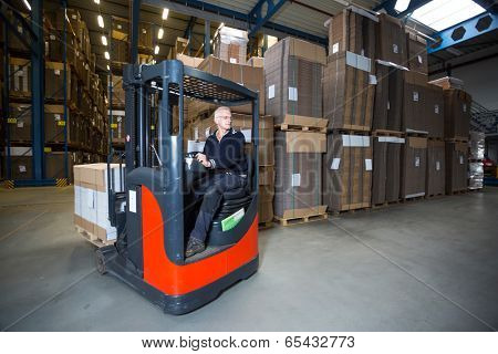 Reach truck driving around the corner in a warehouse where cartboard boxes are stored.
