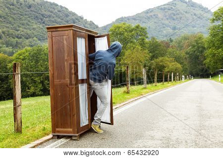 boy looks out of a closet, is in the middle of a road