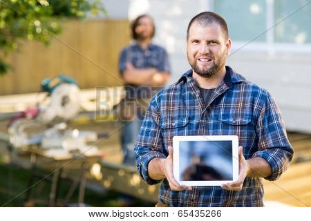 Portrait of mid adult carpenter displaying digital tablet with coworker in background at construction site