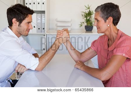 Casual business team arm wrestling at desk in the office