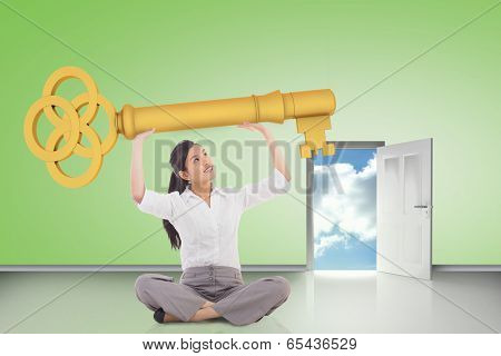 Composite image of businesswoman sitting holding large key against door opening showing blue sky