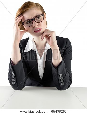Thinking redhead businesswoman looking puzzled on white background