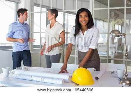 Workers loooking over plans and smiling at camera in the office