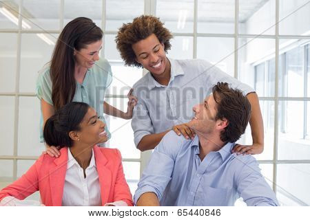 Workers congratulating and praising one another in the office