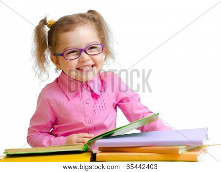 Happy child girl in glasses reading books sitting at table