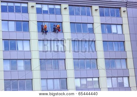 Two Workers Washing A Skyscraper Windows