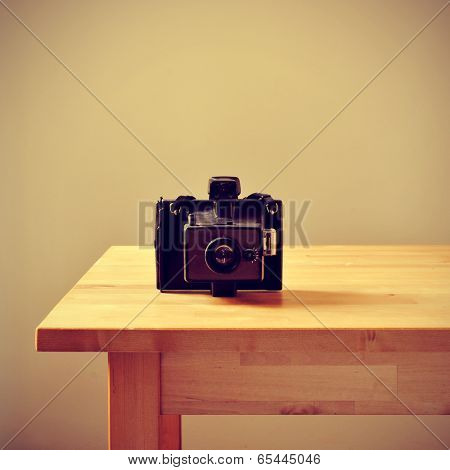 an old instant camera on a table, with a retro effect