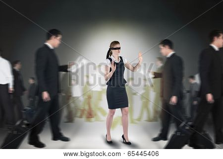 Composite image of redhead businesswoman in a blindfold against grey room