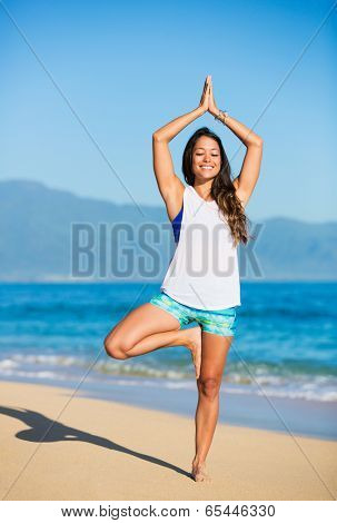 Happy relaxed young woman practicing yoga outdoors at the beach. Healthy active lifestyle. Zen Meditation.
