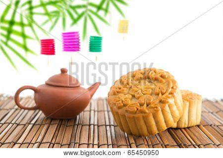 Chinese mid autumn festival foods with blank copy space. Traditional mooncakes on table setting with teacup. The Chinese words on the mooncakes means assorted fruits nuts, not a logo or trademark.