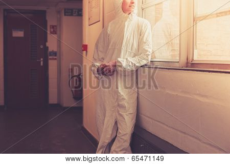 Scientist In Boiler Suit By Window