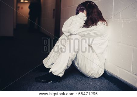 Upset Woman In Boiler Suit Sitting In Corridor