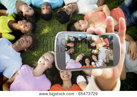 Hand holding smartphone showing multiethnic friends lying down in park