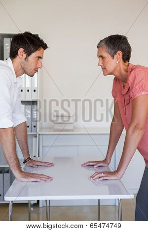 Casual business team facing off at desk in the office