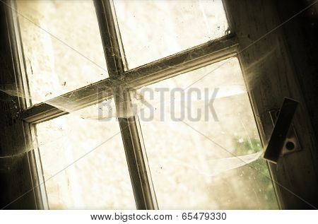 old window with cobwebs