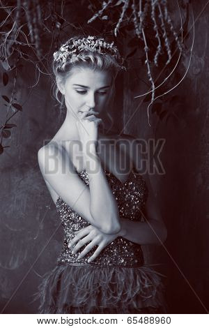 Beautiful blond woman with braid hairstyle and natural makeup. Wearing bohemian sequin and feather dress. Against grunge background. Vintage sepia effect