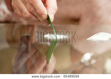 Closeup of a man's hand cutting cocaine on a glass table with a credit card.