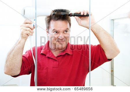 Man blow drying his hair in the bathroom mirror.