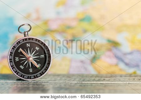 Compass On The Table Against The Background Of A Tourist Map