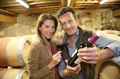 pic of wine cellar  - Cheerful couple of winegrowers in wine cellar - JPG