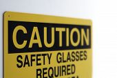 pic of osha  - A yellow caution sign warns of the need for safety glasses - JPG