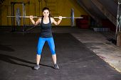 stock photo of squatting  - Cute Hispanic girl doing some squats with a barbell in a crossfit gym - JPG