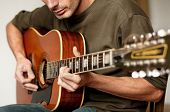stock photo of musical scale  - Hands of a man playing a twelve string acoustic guitar - JPG