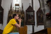 image of humility  - Handsome young man praying in a church - JPG