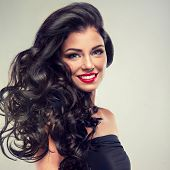 stock photo of  lips  - Model brunette with beautiful long curled hair and red lips - JPG