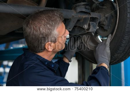 Auto Mechanic Changing At Repair Service Station Car Wheel