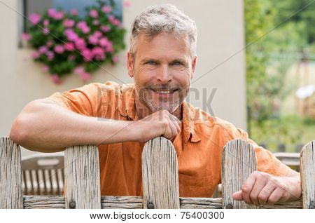 Portrait Of Happy Mature Man Leaning On Fence In Front Of His House