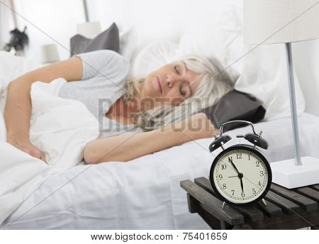 Sleeping woman in front of the alarm clock