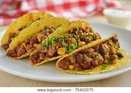 Four tacos with ground beef, red beans, corns, and green onion