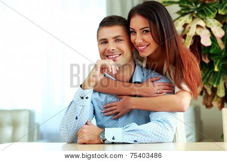Young smiling couple hugging at home