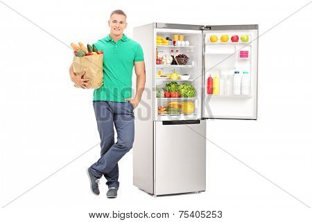 Man holding grocery bag and standing by an open fridge isolated on white background