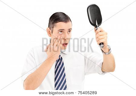 Young man checking his eyelid in a mirror isolated on white background