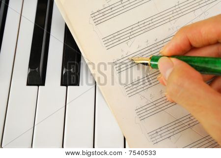 Writing On Old Music Score With Pen On Piano Keyboard