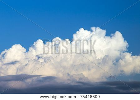 Blue Sky With Puffy And Dark Rain Clouds