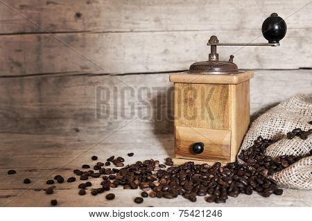 Old Coffee Grinder And Beans On Aged Wooden Background