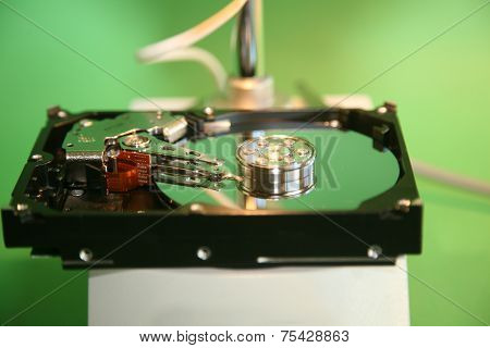 A skilled Computer Technician examines a Computer Hard Drive under a Microscope looking for flaws, scratches in the disc, and other issues to repair or replace. Computer Hard Drives are important