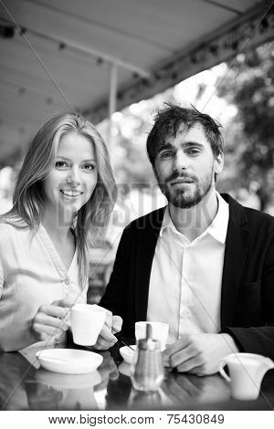 Portrait of calm man and woman having tea or coffee in cafe