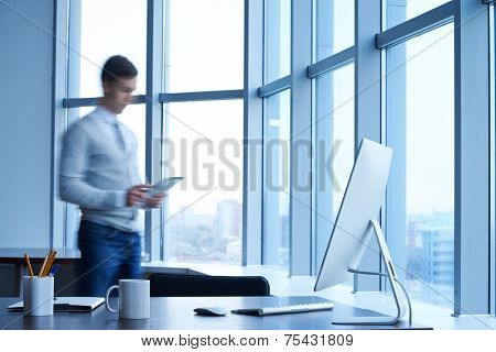 Workplace with computer with young businessman standing near by