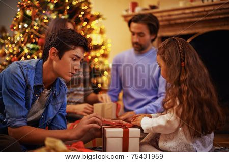 Youthful guy and his sister unpacking giftbox with their parents on background