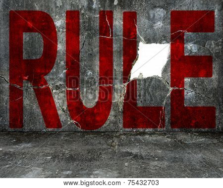 Red Rule Word On Mottled Concrete Wall With Large Hole