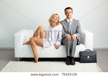 Bored man sitting on sofa with laughing woman looking at him near by