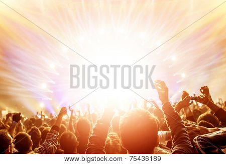 Active happy people enjoying rock concert, many lights from the stage where playing famous musical band, night entertainment concept
