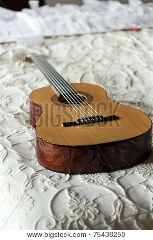 Old Spanish guitar lying on the bed