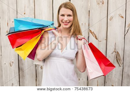 Smiling woman carrying shopping bags over her shoulder in front of a wooden wall