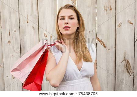Pretty woman carrying shopping bags over her shoulder in front of a wooden wall