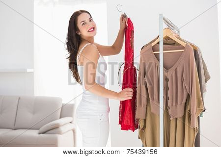Smiling brunette picking out red dress at clothes store